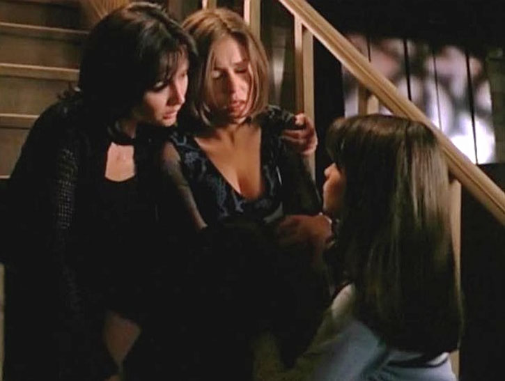 Phoebe Halliwell (Alyssa Milano) sitting on a stair with her sisters