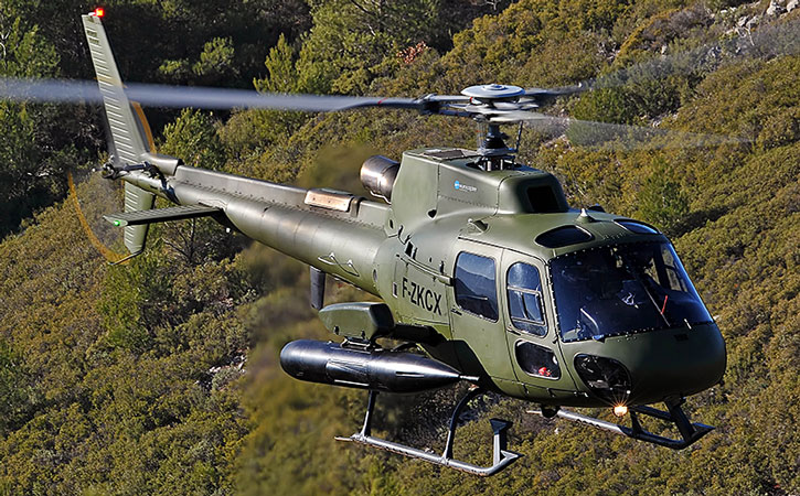 A Fennec helicopter with cannon pods above a mountain