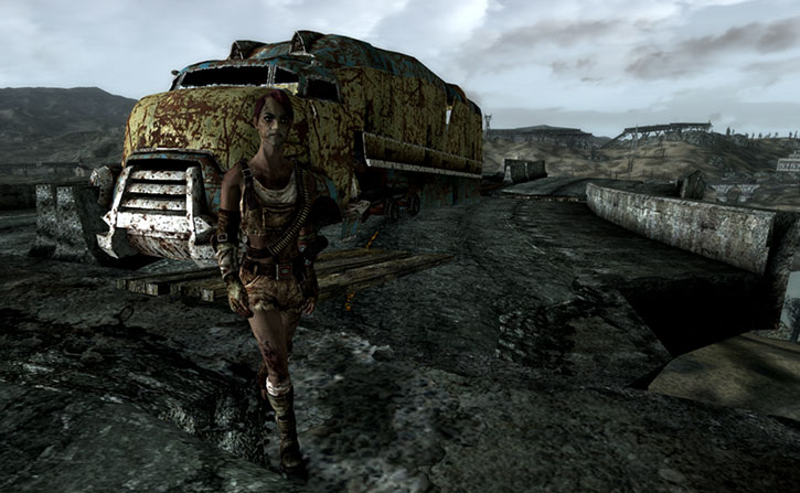 A raider in front of a truck wreck on a ruined overpass
