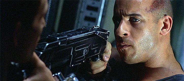 Riddick points a shotgun