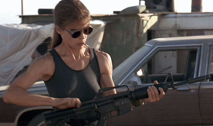 Sarah Connor (Linda Hamilton) checking a M4 assault carbine while smoking