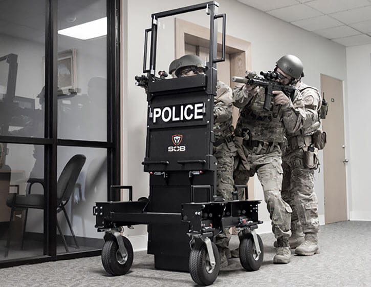 Militarised SWAT officers with a wheeled ballistic shield