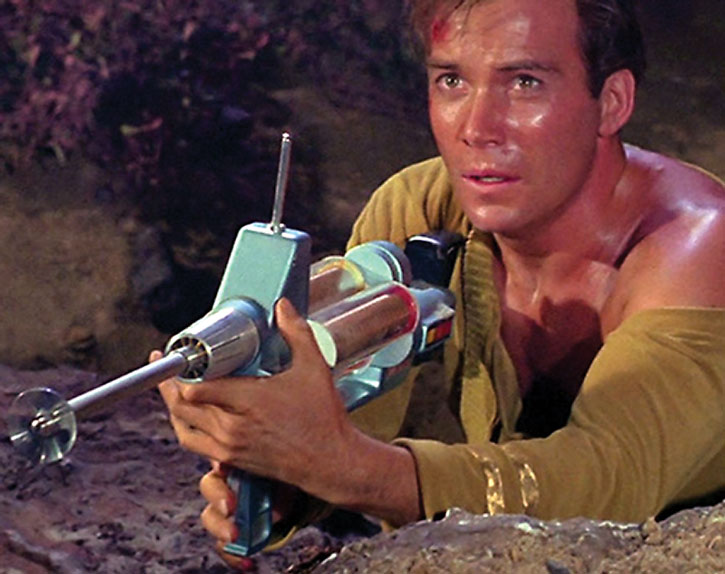 Captain Kirk (William Shatner) with a phaser rifle and a torn shirt