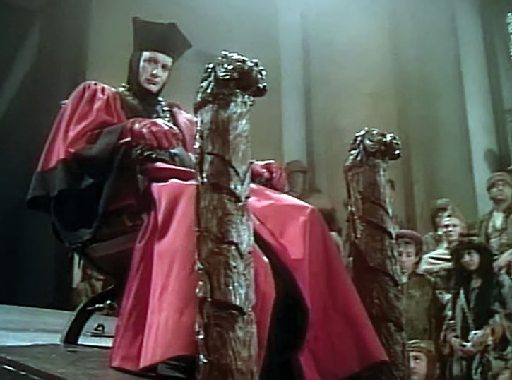Q (John de Lancie) in a red robe on a throne