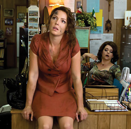 Stephanie Plum (Katherine Heigl in One For The Money) dirty and sitting on a desk