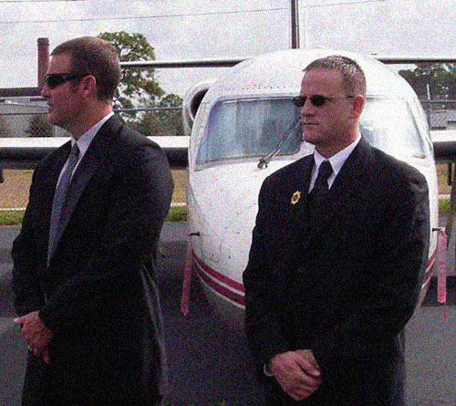 Bodyguards with sunglasses in front of a private jet