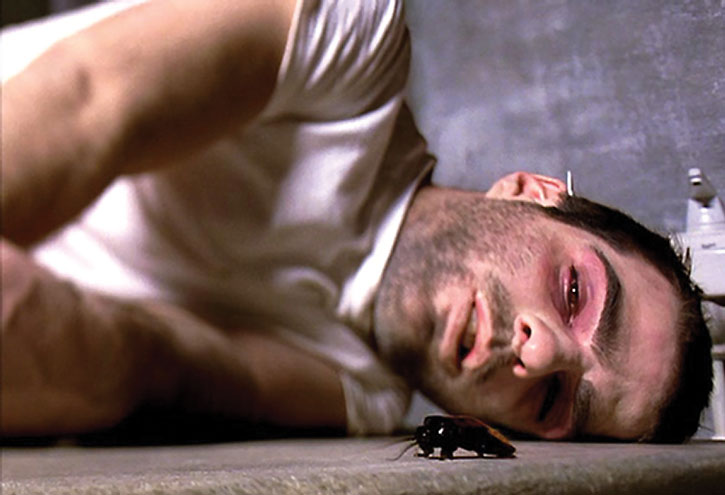 A wrecked Sylar (Zachary Quinto) looks at a cockroach on the floor