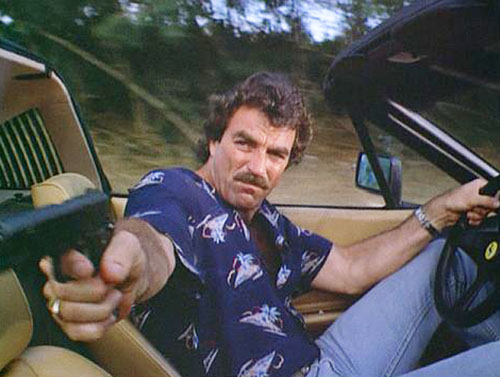 Thomas Magnum (Tom Selleck in Magnum PI) aiming his pistol while driving