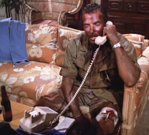 Thomas Magnum (Tom Selleck in Magnum PI) battered and dirty on the phone