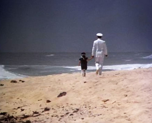 Thomas Magnum (Tom Selleck in Magnum PI) in uniform on a beach with a kid