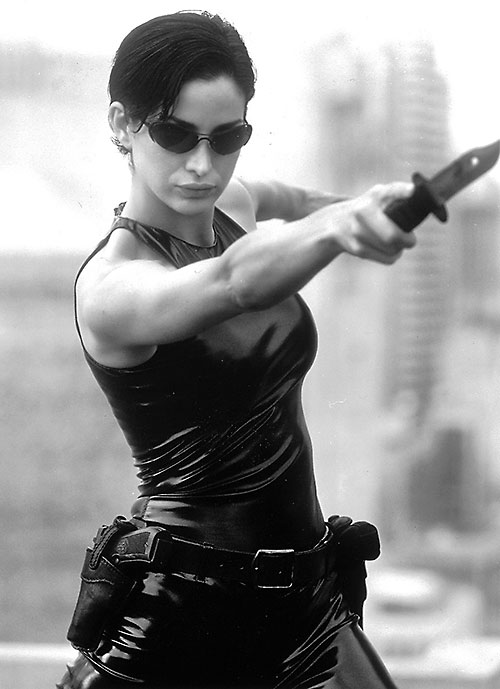 Trinity (Carrie-Anne Moss) throwing a knife