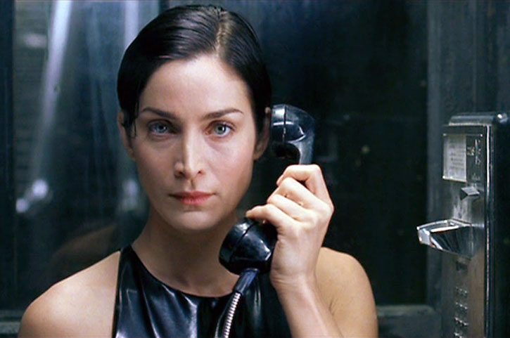 Trinity (Carrie-Anne Moss) in a phone booth
