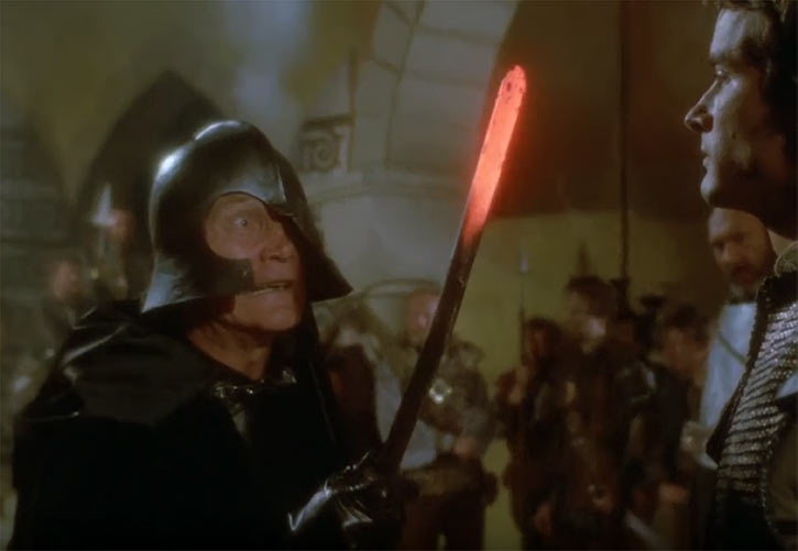 Voltan (Jack Palance in the Hawk the Slayer movie) threatening with red-hot poker