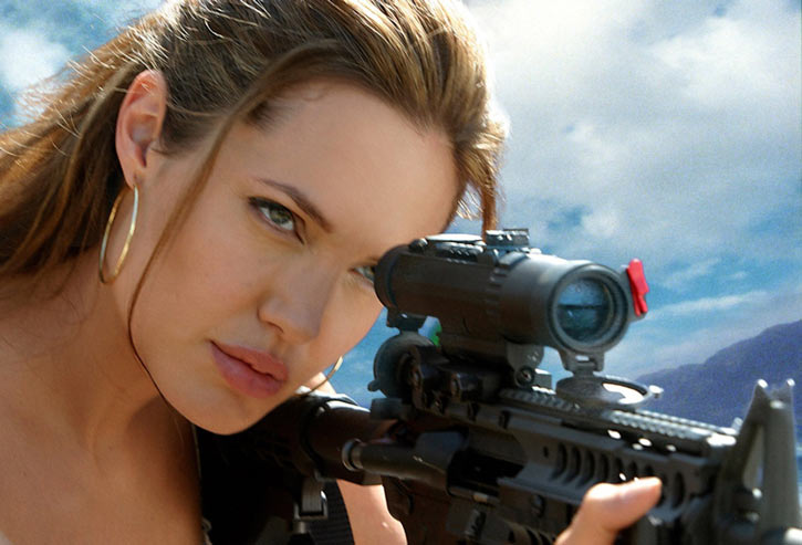 Angelina Jolie aims a scoped carbine