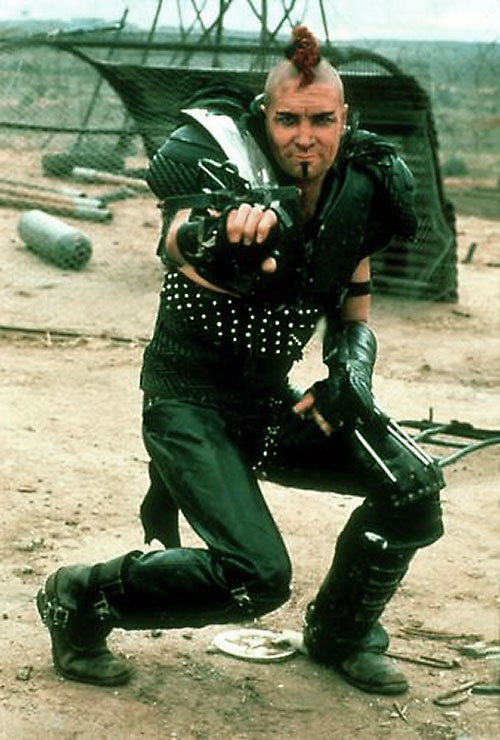 Wez (Vernon Wells in Mad Max) posing with his wrist crossbow