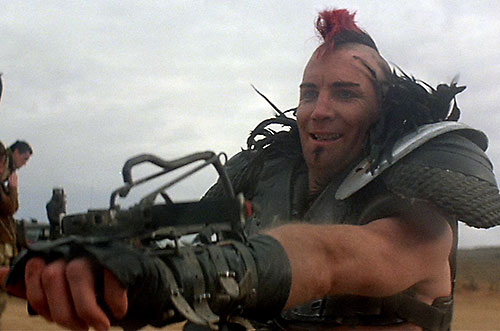 Wez (Vernon Wells in Mad Max) pointing his wrist crossbow